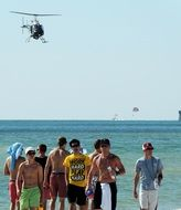 a group of students on the background of the sea and a flying helicopter