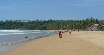people resting on sand beach, india, goa, bogmalo
