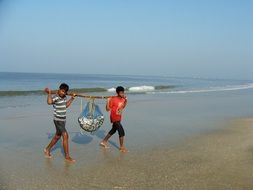 fishermen with their catch are on the sea beach of Goa