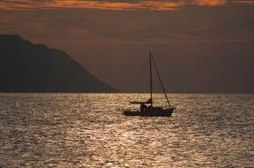 sailing boat in the ocean at sunset