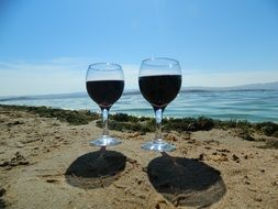 two glasses of wine on a sandy beach