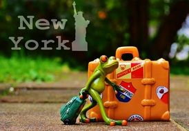 statuette of a frog with a bag near a suitcase in new york