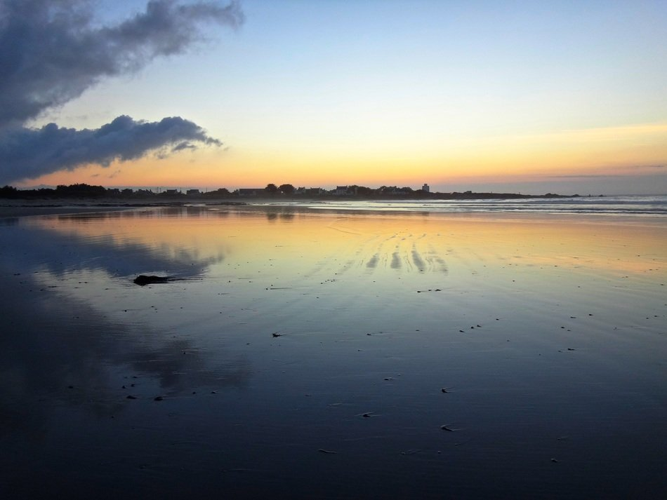 beautiful sunset mirroring on beach at sea, france, brittany