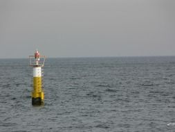 Yellow and white lighthouse in the Pacific Ocean off the coast of Costa Rica