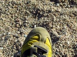 leg in sport shoes on a sandy beach close up