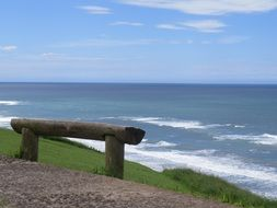 wooden bench made of logs by the sea