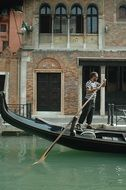 man with paddle in gondola on canal, italy, venice