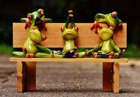 relaxed ceramic frogs on the bench