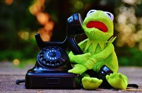 figure of a green frog with a black phone