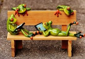 ceramic frogs relaxing in the bench