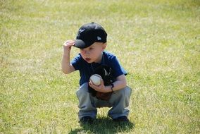 baby with a ball on green grass