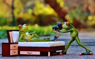 ceramic figures of frogs conduct a photo shoot