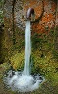 ancient rusted fountain, waterjet falling on moss