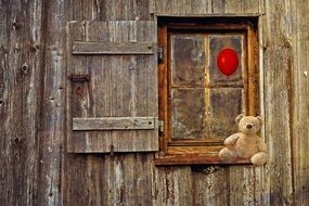 Tteddy bear on the window of a wooden house
