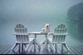Teddy Bear on table outdoor at rainy weather