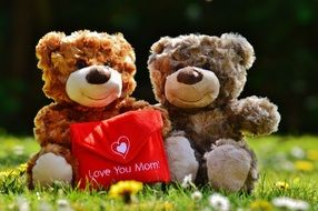 an envelope with an inscription love for mom in the hands of teddy bears