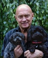man with two black puppies