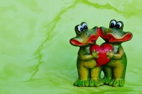 ceramic figurine of two frogs holding heart