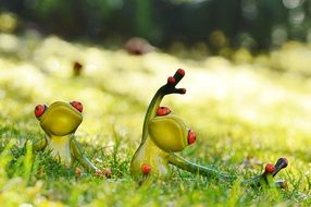 two ceramic frogs do yoga on the meadow