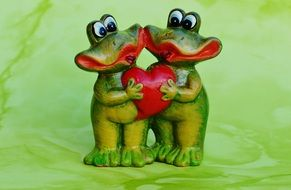 two ceramic frog with a heart in his hands