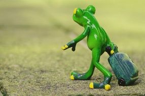 green frog figure with luggage