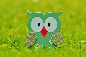 wooden figure of a owl in green grass
