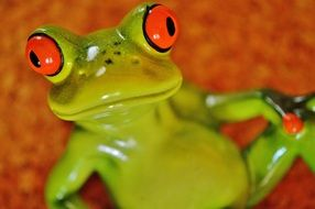 ceramic green frog with big red eyes