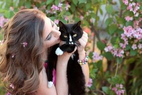young woman kissing black cat