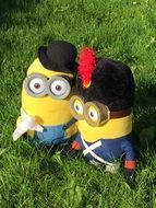 two plush minions on green grass