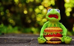 Kermit is sitting on the floor with cheeseburger