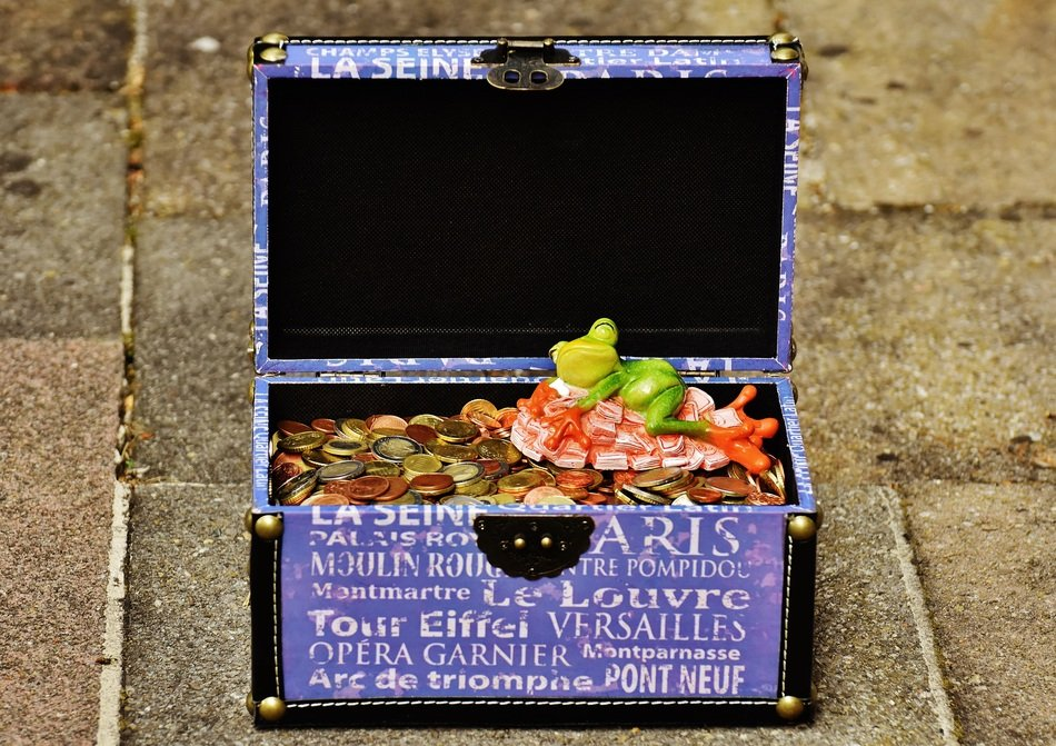 figurine frog lies in a chest with coins