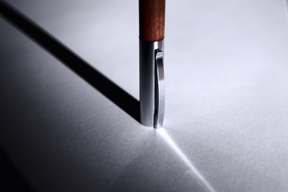 the shadow of the pen on the table