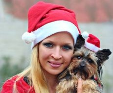 woman and yorkshire terrier with santa claus hat