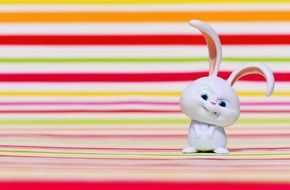 angry white rabbit on a background of colored bands