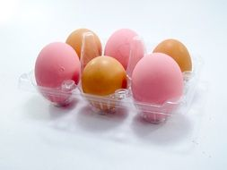 yellow and pink eggs in a box