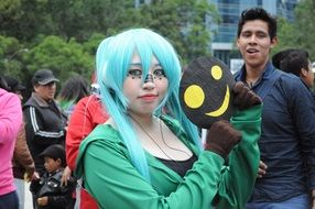 young lady in cosplay costume and blue wig