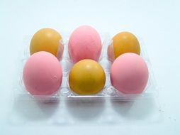 yellow and pink eggs in an egg carton