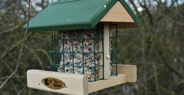 wooden aviary with a green roof for birds