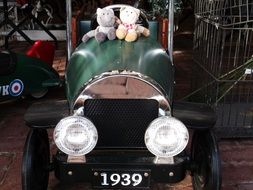 two soft toys on a retro car