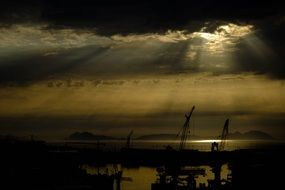 panoramic view of darrk sunset over port cranes