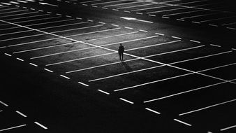 distant view of a lonely man among the parking at night