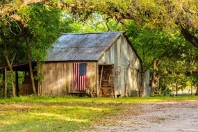 old wooden Barn with usa flag on wall in Country Landscape