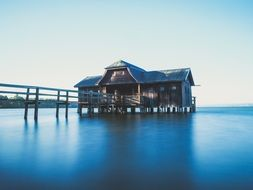 wooden house with boardwalk on calm water