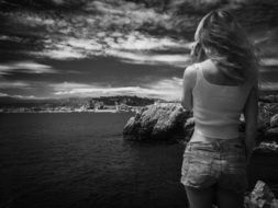 black and white photo of a girl on a rocky shore in Monaco
