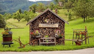 welcome, decoration with wood pile, plows and flowers at garden