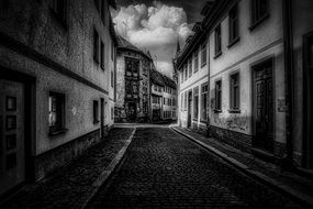 black and white photo of paved street in Erfurt, Germany with clouds in the sky