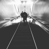 black and white photo of people climbing the escalator