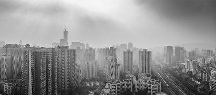 black and white photo of city skyscrapers in the fog