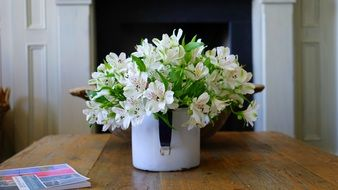 white fresia flowers in mug on wooden table