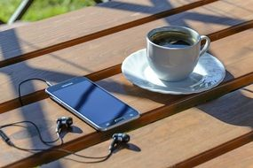 Relaxation, Coffee and Smartphone on table outdoor